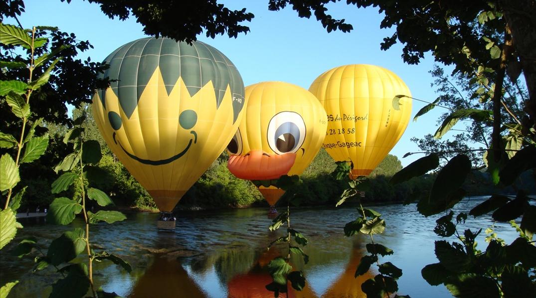 Photo de 3 montgolfières qui survolent la Dordogne