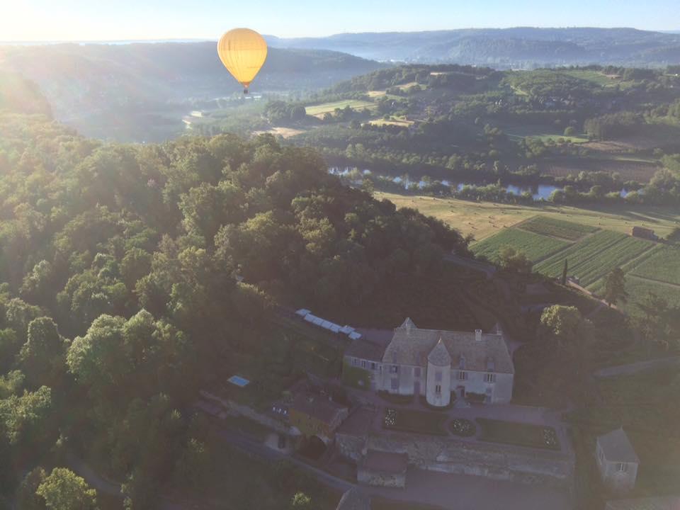 Photo représentant une montgolfière survolant le chateau de Marqueyssac et la vallée de la Dordogne