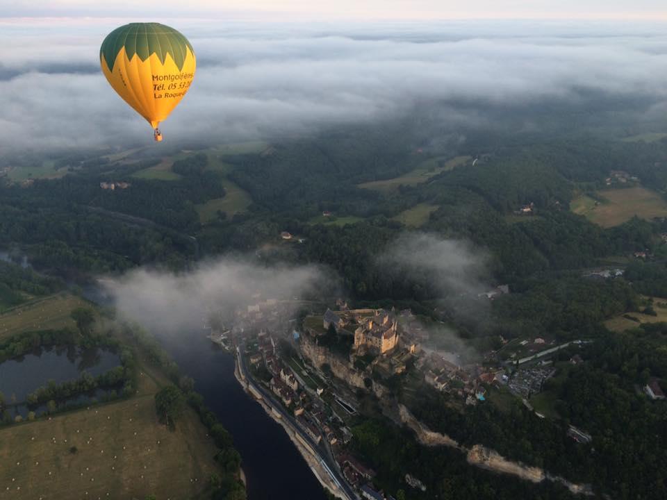 Photo représentant une montgolfière survolant la vallée de la Dordogne et le chateau de Castelnaud-la-Chapelle