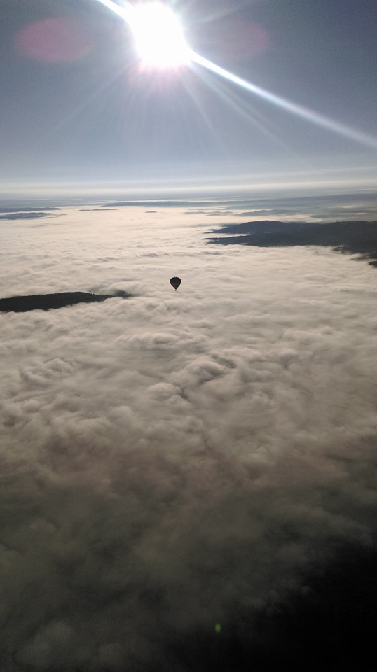 Photo représentant une montgolfière au dessus des nuages à l'aube, en Périgord