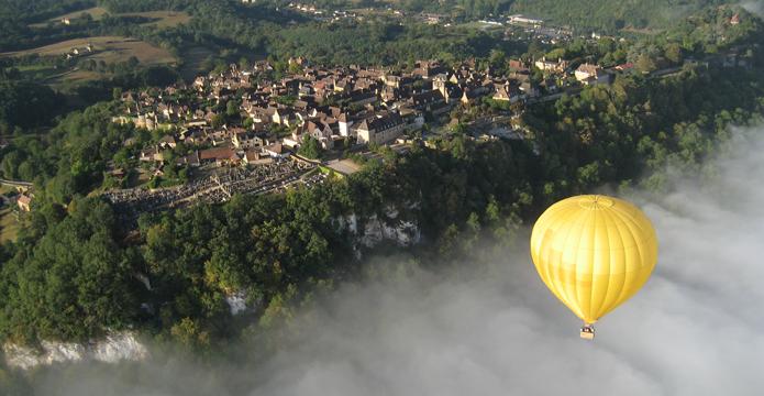 Photo vue sur une ville et une montgolfière du Périgord